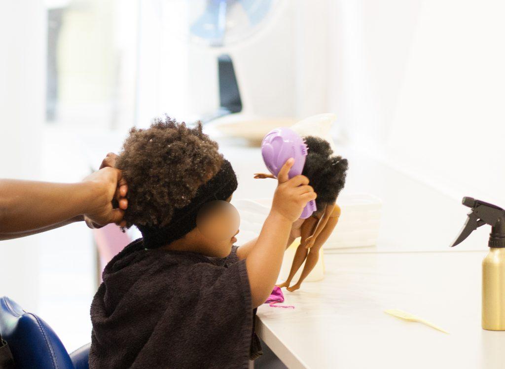 Enfant coiffe sa poupée aux cheveux crépus